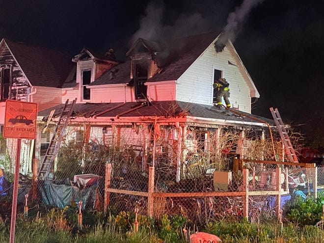 A Muncie firefighter enters a second-story window late Friday while battling a blaze in a house at 1600 N. Shirey Road.