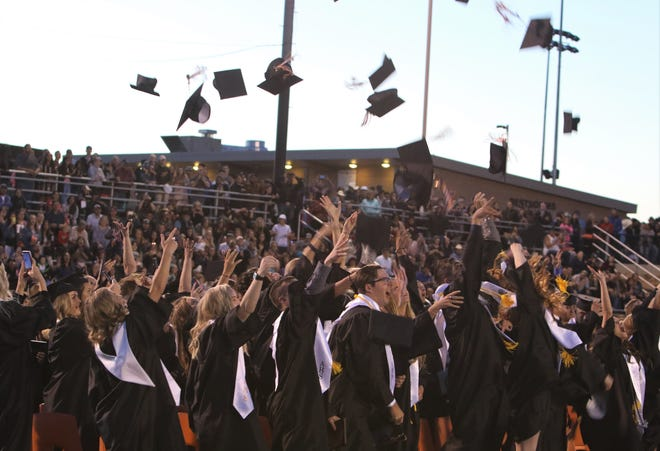 Aztec High School graduates toss their caps into the air on May 24, 2019. Loosened COVID-19 restrictions mean the school can hold an in-person graduation ceremony this year, with guests, at Fred Cook Stadium.