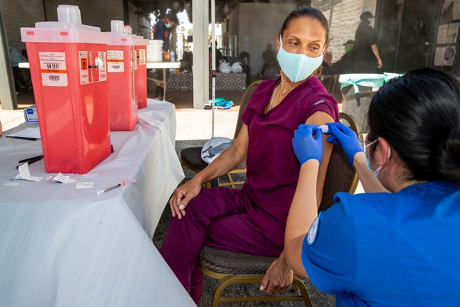 Marianne Lofton receives a first dose of the COVID-19 vaccine during the CSUSB Nursing Street Medicine Program's mobile vaccine clinic outside the Well in the Desert in Palm Springs, Calif., on May 7, 2021.