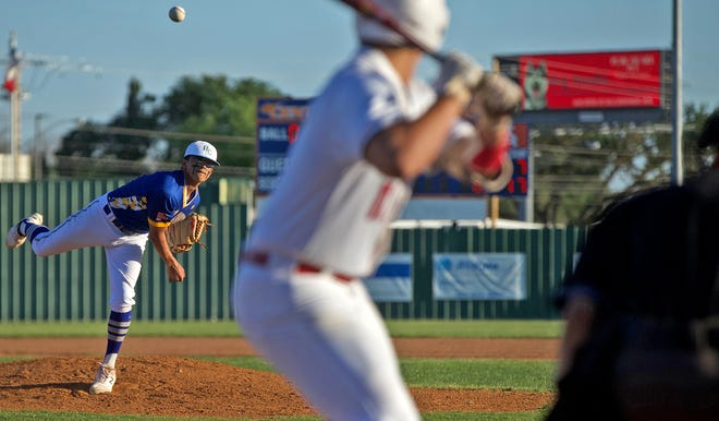 Jacob Gallegos, far left, delivers a pitch to the plate for Reagan County during a game against Ballinger on Friday, May 7, 2021.