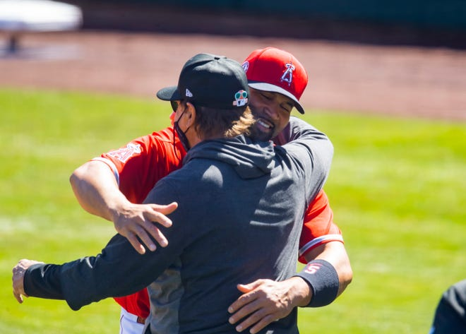 Los Angeles Angels first baseman Albert Pujols (right) hugs Chicago White Sox manager Tony La Russa prior to a 2021 spring training game at Tempe Diablo Stadium.
