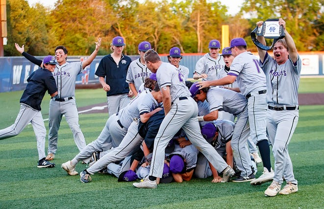 """Cedar Ridge's Nick Zamora holds up the """"Raiders of the Week"""" belt as players dogpile in celebration following their 8-5 win over the Westlake Chaparrals in the third an final game of the Class 6A bi-district playoff series Saturday at Westlake High School. After losing the first game of the series, Cedar Ridge won both games Saturday to advance to the second round of the playoffs."""