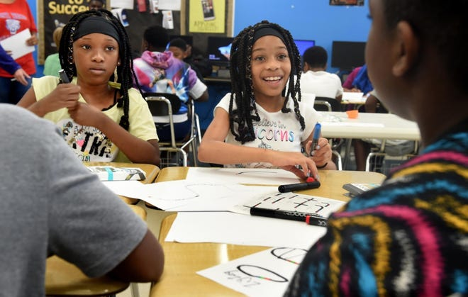 Makayla Cushman, 11, (left) and Seryah Scriven, 9, work on programming their Ozobot robots during a 2019 summer Cyber Camp at Richmond County Technical Career Magnet School.