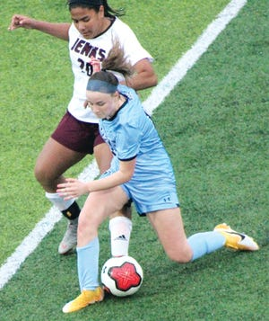 A Bartlesville High player, right, obstructs the path of a Jenks High athlete during varsity girls soccer action last month.