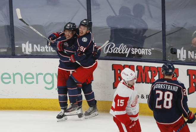 Blue Jackets forwards Max Domi, left, and Jack Roslovic celebrate Domi's winning goal late in overtime in a 5-4 victory over Detroit on Saturday in both teams' season-finale.