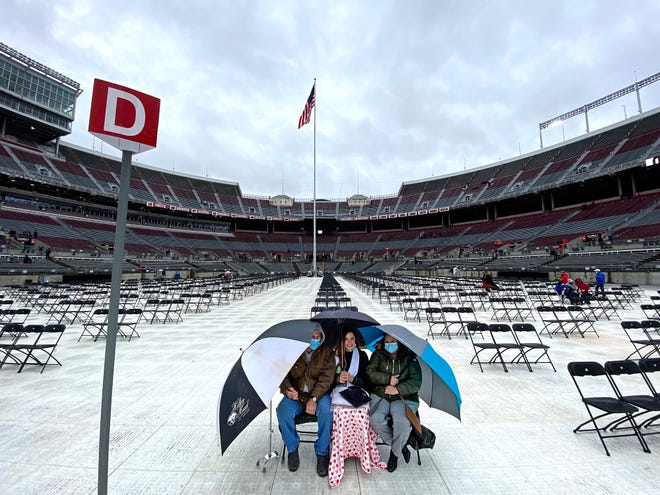 The Humphreys from Jackson, Ohio, wait for Ohio State University's spring commencement to begin Sunday. From left: Dad Charles; graduate Alexandrea (animal science major) and mom Tricia sit under umbrellas at Ohio Stadium in Columbus.