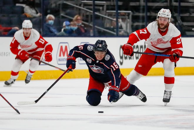 Columbus Blue Jackets center Max Domi (16) falls to the ice in front of Detroit Red Wings center Michael Rasmussen (27) during the first period of the NHL hockey game in Columbus on Saturday, May 8, 2021.