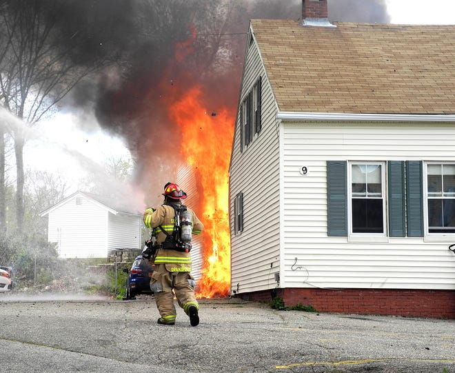 Firefighters prepare to fight a blaze at a multiple-unit building at 9 Linden St. in Somersworth about noon Sunday, May 9, 2021.