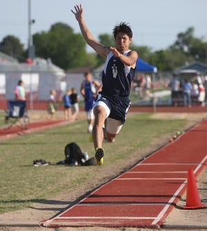 TMP's Ian Chiu glides through the air in the long jump on Friday in Russell.