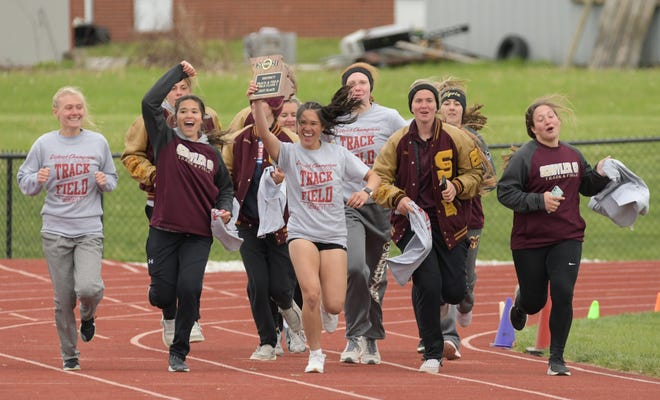 Schuyler County's Emma Clifford holds up the Class 1 District 3 trophy as the team runs a celebratory victory lap.