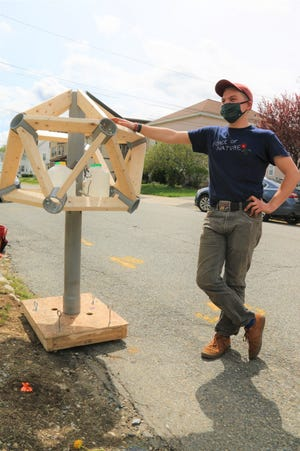 Growing Places Environmental Sustainability Coordinator Kyle Anderson with his handiwork, a watering station he designed and crafted out of repurposed wood and PVC pipes.