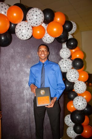 Pawhuska High School junior Mason Gilkey, shown here accepting a basketball rebounding award at the annual All Sports Banquet, won 2A state track and field titles in the 200-meter dash and the 400-meter run.