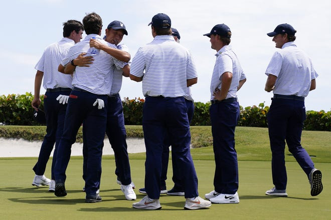 Members of the US team celebrate after Cole Hammer and Davis Thompson won their match against Great Britain and Ireland team on the 18th hole in the foursome matches during the Walker Cup golf tournament at the Seminole Golf Club on Saturday in Juno Beach.
