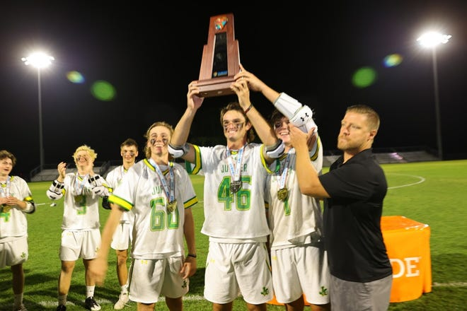 Jupiter celebrates with the championship trophy after winning the Class 2A boys lacrosse state championship Saturday night.