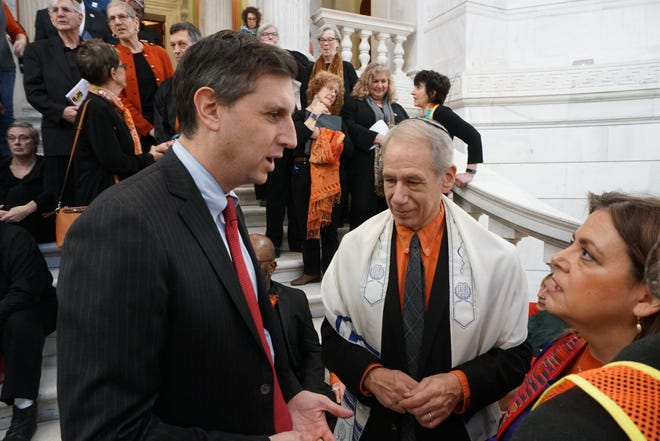 General Treasurer Seth Magaziner speaks with the Rev. Liz Lerner Maclay before a rally against gun violence at the State House last year. At center is Rabbi Howard Voss-Altman of Temple Habonim.