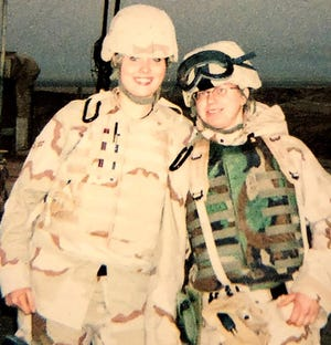 Air Force Security Forces Airmen Rachael Garcia, left, poses with fellow service member Danielle Davis, right, in 2006 at Tallil Air Base in Iraq.