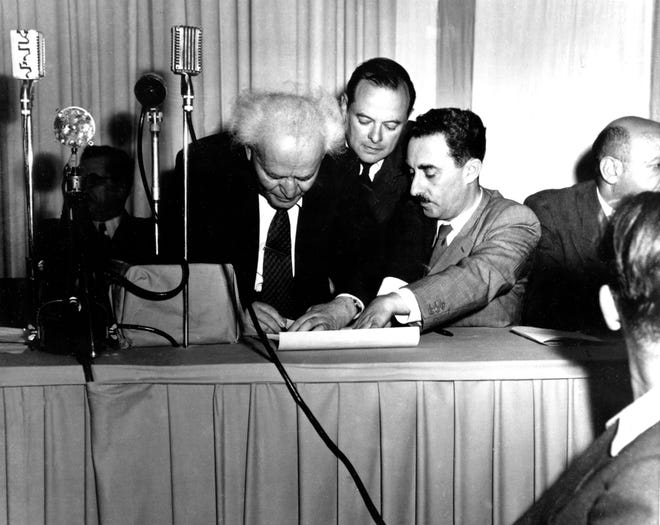 Israeli Prime Minister David Ben-Gurion, left, signs a document in Tel Aviv, Palestine, proclaiming the new Jewish state of Israel in Tel Aviv at midnight on May 14, 1948. Witnessing the ceremony at right is Israel's first Foreign Minister Moshe Sharett, Zionist pioneer and leader in the establishment of the state of Israel. The man at center is not identified.