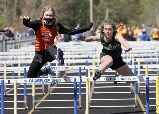 Marcellus' Madilyn Simpson and Mendon's Alivia Stuart leap over the final hurdle Saturday. Stuart finished second, just ahead of Simpson.