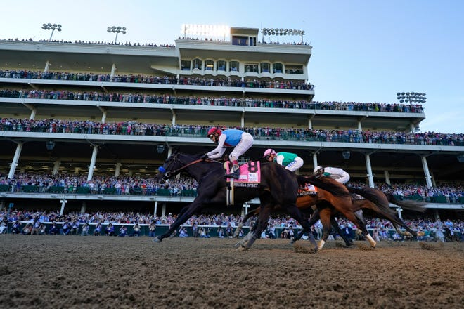 John Velazquez riding Medina Spirit leads Florent Geroux on Mandaloun and Flavien Prat riding Hot Rod Charlie to win the 147th running of the Kentucky Derby at Churchill Downs, May 1 in Louisville, Ky.