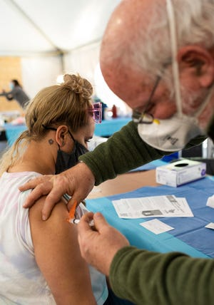 Retired doctor Robert Terrill administers the COVID-19 vaccine to Keichmarie Negron during a May vaccination clinic in Worcester.