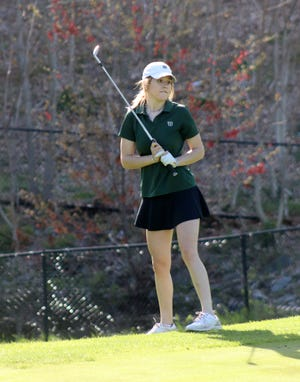 Wachusett senior captain Jackie Brewer chips to the seventh green and watches her shot roll toward the hole.