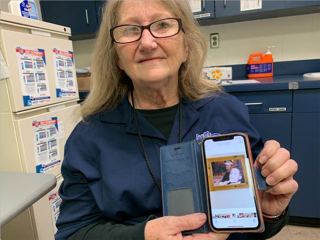Sherryl Grubb holds up a photo of a painting she made of son Scott on a family cruise in the First Aid department at Principal Park in Des Moines on Friday, May 8, 2021.