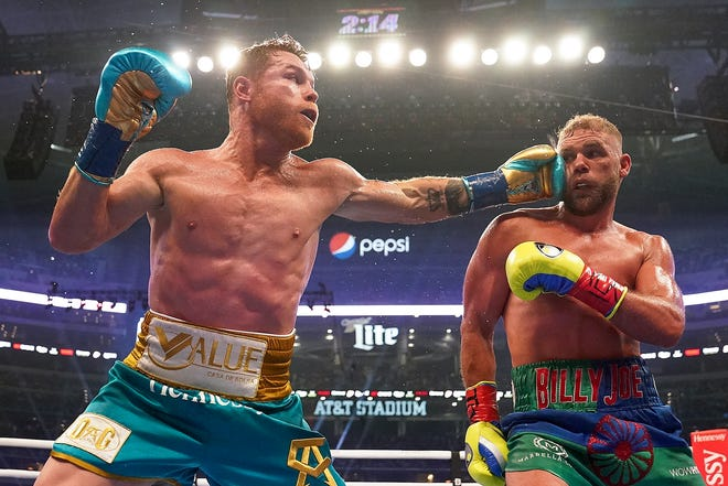 Canelo Alvarez, left, connects against Billy Joe Saunders during a unified super middleweight world championship boxing match, Saturday, May 8, 2021, in Arlington, Texas.