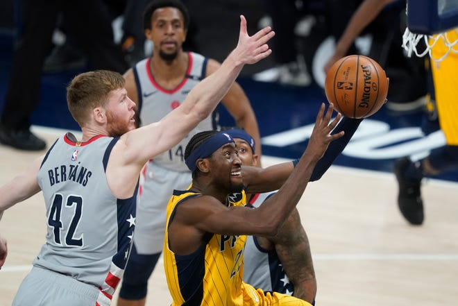 Indiana Pacers' Caris LeVert (22) puts up a shot against tWashington Wizards' Davis Bertans (42) during the second half of an NBA basketball game, Saturday, May 8, 2021, in Indianapolis. (AP Photo/Darron Cummings)