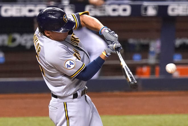 The Brewers' Tyrone Taylor hits a RBI-single that scores Kolten Wong during the third inning against the Marlins.