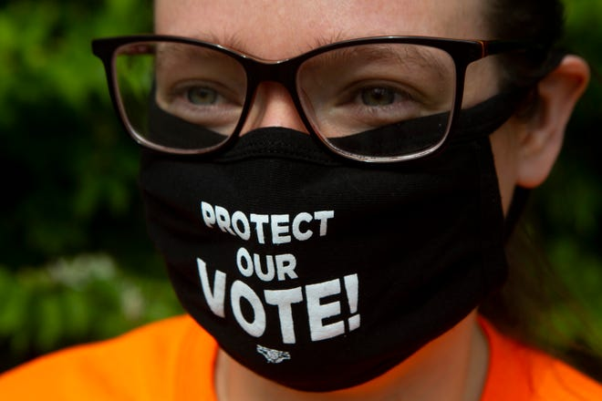 A voting-rights advocate carries a message on a mask during the John Lewis Voting Rights Advancement Action Day in Reynoldsburg on May 8.