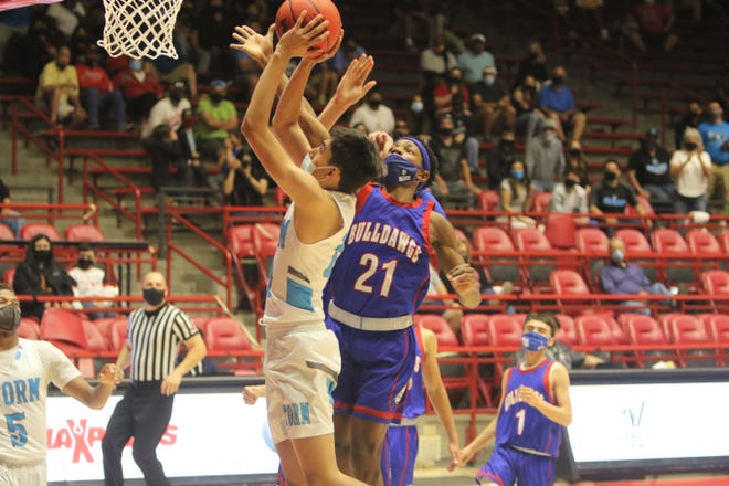 Las Cruces' Deuce Benjamin blocks a layup attempt by Cleveland's Cole Savage during the 5A state basketball finals on Saturday, May 8, 2021, at The Pit in Albuquerque.