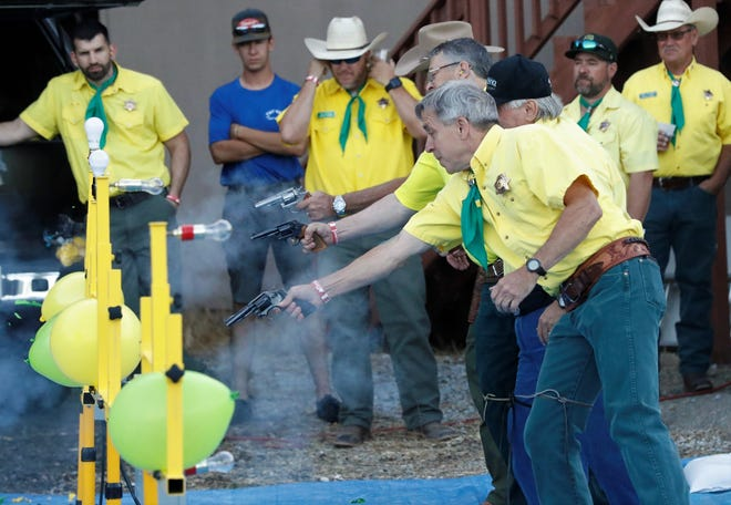 Troy Spade and fellow Asphalt Cowboys draw their guns and fire blanks at balloons in the Quick Draw Contest on Friday, May 7, 2021, outside their clubhouse. The fast-draw competition was held during the traditional street dance.
