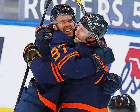 Edmonton Oilers striker Connor McDavid celebrates with Leon Draisaitl after Draisaitl's goal late in the second period.  McDavid got his 100th point of the season with an assist on goal.