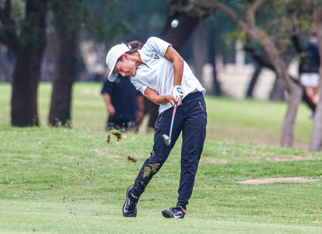Vandegrift's Mimi Burton hits an iron on the 18th hole during the first round of the Class 6A girls golf tournament on Monday at Legacy Hills Golf Club in Georgetown. Burton is tied for the lead after the first round at the two-round event, and she helped the Vipers lead the team standings.