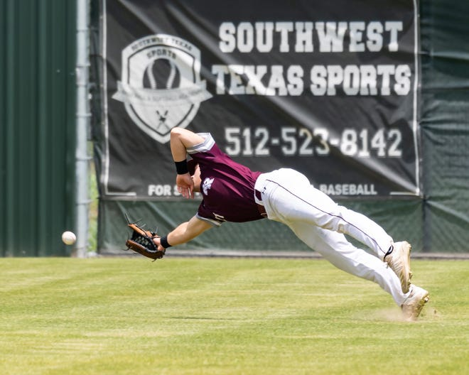 Round Rock right fielder Parker Kuhn dives for a ball against Hays in a 19-4 win over Hays Saturday at Hays High School. Round Rock swept the best-of-three playoff series to reach the second round.