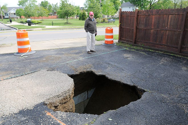 Ed Miller checks out the sinkhole in the parking lot next to his home on East Main Street on Monday, May 10, a day after almost 3 inches of rain fell on Ashland.
