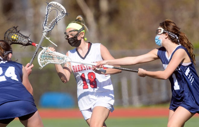 Katy Shaw of Barnstable moves with the ball as Hannah Evens (24) and Brooke Damian (1) of Nantucket close in.