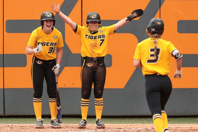 Missouri catcher Hatti Moore (31) and center fielder Brooke Wilmes (7) celebrate with shortstop Jenna Laird (3) during a game against Tennessee on Sunday in Knoxville, Tenn.