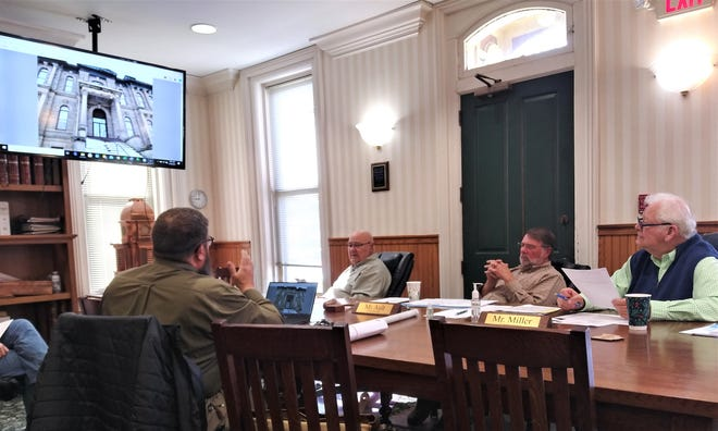 Holmes County Commissioners (from left) Ray Eyler, Rob Ault and Joe Miller, listen and look on at a presentation about needed repairs to the Holmes County Courthouse by Midstate Contractors President Doug Hooper Monday morning in Millersburg. Midstate is currently renovating the clock tower, and provided a report on the building structure at the request of the commissioners.