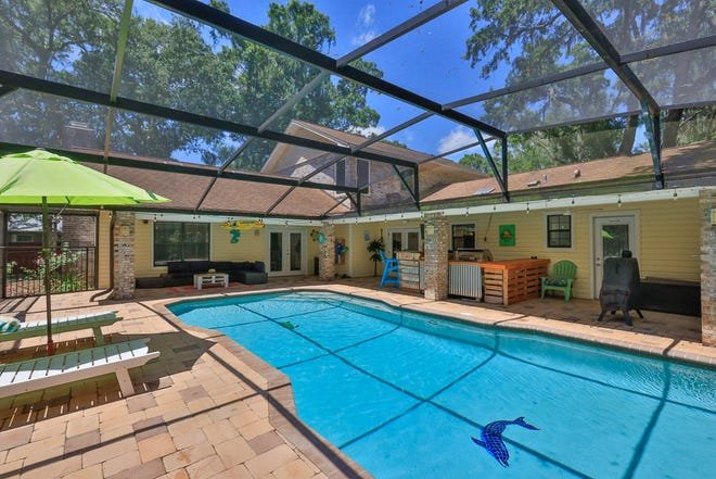 Two sets of glass French doors lead out to the outdoor living space, featuring a covered lanai, heated saltwater pool, built-in barbecue, refrigerator and bar.