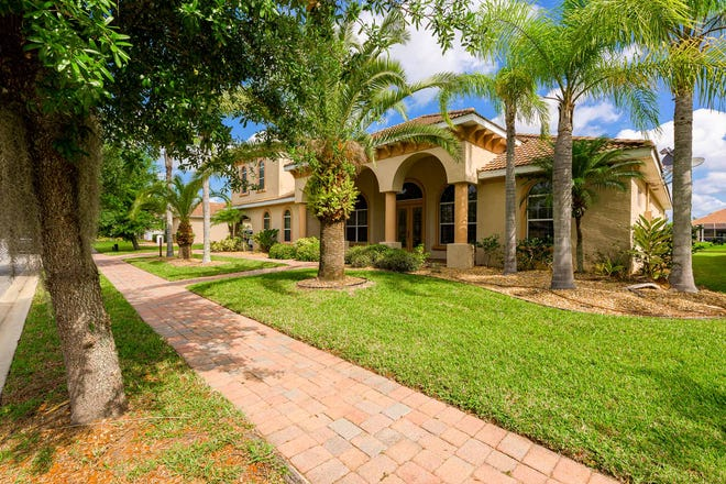 Enveloped in a sea of tropical trees, this lakefront masterpiece is located in the prestigious Venetian Bay gated community of Tuscany Reserve.