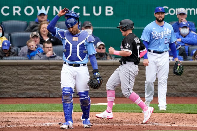 Kansas City Royals catcher Salvador Perez, left, and pitcher Jakob Junis look on as Chicago's Andrew Vaughn crosses home plate in the sixth inning of Sunday's game at Kauffman Stadium. The Royals lost 9-3, their eighth straight loss and 10th straight at home to the White Sox.