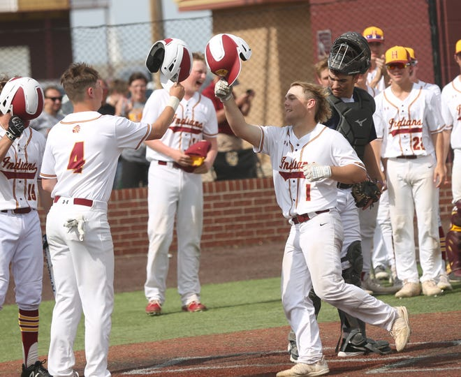 Dalton Dale (1) is greeted by Garrett Wellbrock (4) after Dale's home run during Hays High's 9-0 win over Manhattan in Saturday's Diamond Classic final.