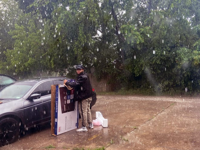 A Sherman man braves falling hail Monday while attempting to cover his car during a brief storm that moved through the area dropping pea sized hail in some places (Jerrie Whitele /Herald Democrat).