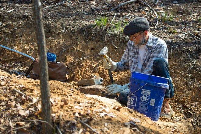 Stefan Israel crushes rocks for gravel.