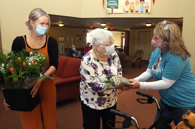 Carol Fortner, center, accepts a wrapped tulip floral arrangement from Brooke Deininger, right, as Hattie Archer, lefts holds other bouquets given out Sunday, May 9, 2021, at Heritage Woods in Freeport.