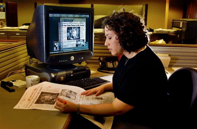 Amy Raymond checks a printed proof after laying out a page on her computer in this undated photo.