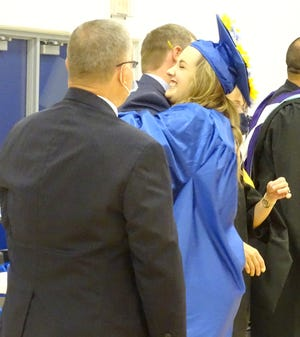 West Franklin senior Ainsley Corwine receives a big hug after receiving her diploma Saturday in the high school graduation ceremony. There were 42 Falcons in the Class of 2021.