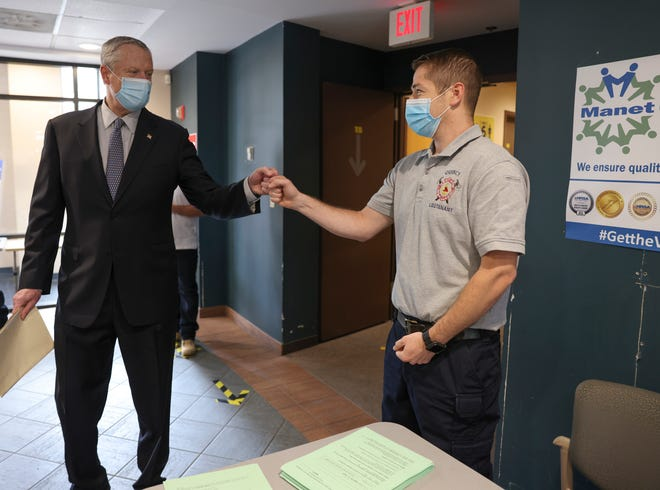 Governor Charlie Baker, fist bumps Quincy Fire Lt. Joseph Ceurvels before touring the Manet Community Health Center Vaccination Site inside the Manet Community Health Center.