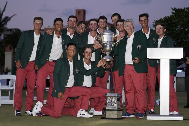 The USA team poses with the trophy after winning the Walker Cup on Sunday at Seminole Golf Club.